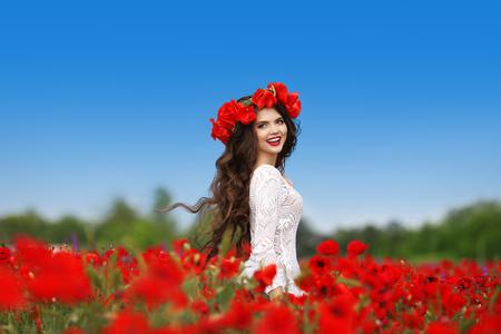 alegria: Disfrute. Hermosa mujer Morena despreocupada con el pelo sano largo que se ejecuta en el fondo rojo de las amapolas campo cubo. Bienestar bienestar concepto de la felicidad. Foto de archivo