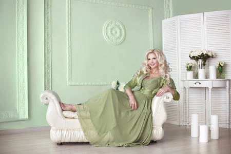 gown: Beautiful smiling elegant blond woman with long curly hair style wears in green dress posing on modern sofa at home interior. Fashionable lady in glamour gown.