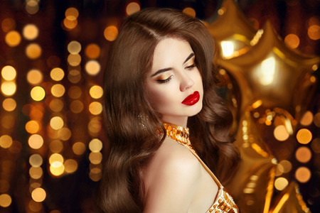 Elegant sexy girl portrait in gold. Makeup. Fashion brunette lady with red lips. Long wavy hair. Beautiful glamour woman in fashionable dress posing over golden party lights boker background.