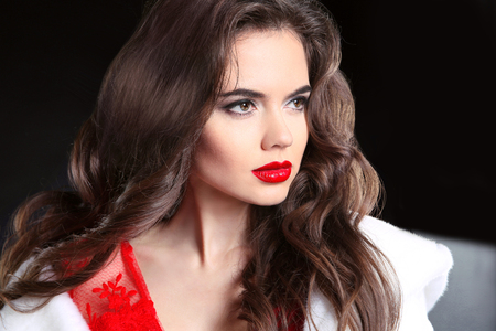 Red lips makeup. Beautiful brunette portrait. Fashion girl model with long curly hair style in red dress with white fur coat isolated on black studio background. Beauty closeup. Stock Photo