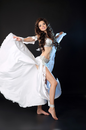 sexy dancer: bellydance. Beautiful Arabic sexy belly dancer in blowing white dress dancing isolated on black studio background. Attractive smiling Turkish female performer artist.