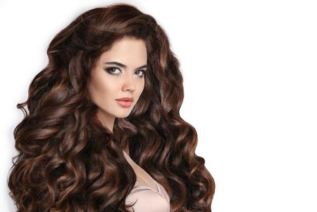 ブルネット。髪は長い。巻き毛のヘアスタイル。スタジオ白い背景に分離された波状の健康な髪と美しい女性。美容化粧。シャンプーのヘルスケア