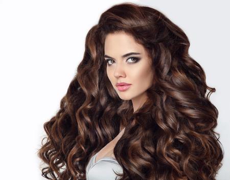 Cheveux longs. Beau portrait de femme de brune avec des cheveux brillants bouclés isloated sur fond blanc studio. maquillage de beauté. Shampooing santé.