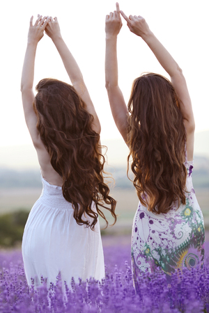 Beautiful young two women over a violet lavender field in Provence at sunset Stock Photo