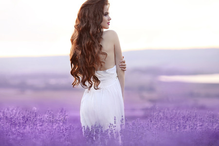 Beautiful young woman portrait in lavender field. Attractive brunette girl with long curly hair style in white dress dreaming. Zdjęcie Seryjne - 68922605