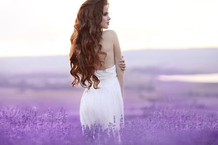 Mooie jonge vrouw portret in lavendel veld. Aantrekkelijke brunette meisje met lang krullend haar stijl in witte jurk dromen.