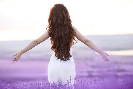 Mulher morena livre com os braços abertos, apreciando o pôr do sol no campo de lavanda. Harmonia. Garota atraente com estilo de cabelo longo encaracolado em vestido branco sonhando. Foto de archivo