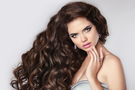 Сurly hair. Beautiful brunette woman model with makeup, fashion jewelry set. Attractive young female with long healthy wavy hairstyle isolated on studio grey background. Imagens