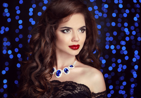 Beauty fashion portrait of elegant woman with red lips makeup, healthy curly hair style and necklace jewelry over blue bokeh party lights ob black background.