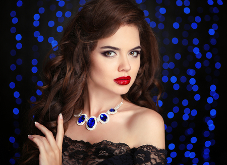 Beauty portrait of elegant woman with red lips makeup, healthy curly hair style and necklace jewelry over blue bokeh party lights ob black background.