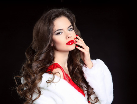 red hair beauty: Beautiful Fashion brunette Girl portrait in white Mink Fur Coat. Red lips makeup. Beauty Luxury winter woman with long curly hair style posing isolated on studio black background. Stock Photo
