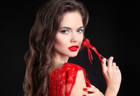 Red lips. Beautiful brunette girl portrait holding heart gift for Valentines Day. Sensual woman with long hair style isolated on black background.