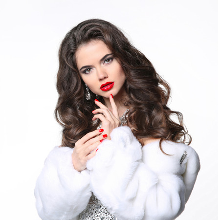 Beautiful brunette girl in white fur coat. Winter fashion beauty portrait. Attractive woman model with red lips makeup and long curly hair posing isolated on white studio background. Stock Photo