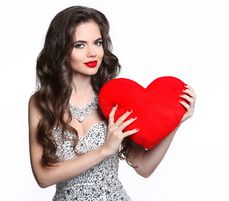 red hair beauty: Beautiful smiling girl with valentine heart  isolated on white background. Attractive brunette woman posing in red dress. Beauty makeup. Long healthy curly hair. Manicured nails. Stock Photo