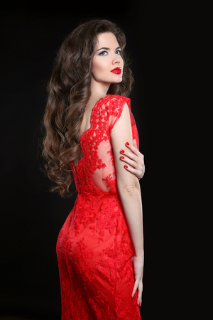 red hair beauty: Beautiful sexy woman posing in red dress isolated on black background. Beauty makeup. Long healthy curly hair.  Fashion style studio photo. Manicured nails.