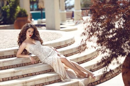 Fashion elegant lady in dress lying on steps. Beautiful young brunette woman with curly hair and evening makeup, wears luxurious party dress and bijou. Outdoor photo portrait.