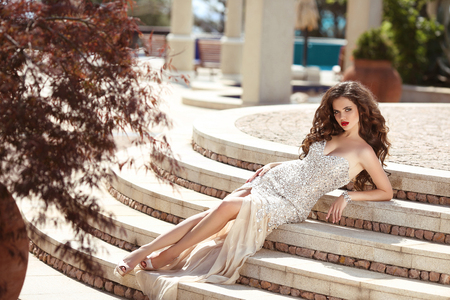 Fashionable sexy woman in luxury dress. Beautiful young brunette with curly hair lying on steps. Elegant fashion style glamour summer photo.  Stock Photo