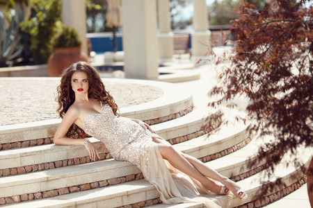 Fashionable sexy woman in dress lying on steps. Glamour and fashion style. Beautiful young brunette with curly hair and evening makeup, wears luxurious party gown.