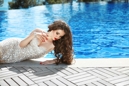 Beautiful woman in Elegant dress. Sexy brunette lying by blue swimming pool. Fashion outdoor portrait. Luxury resort. Cute girl model with red lips makeup and long curly hair. Stock Photo