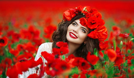 Beautiful happy smiling teen girl portrait with red flowers on head enjoying in poppies field nature background. Makeup and curly hair style. Stock Photo