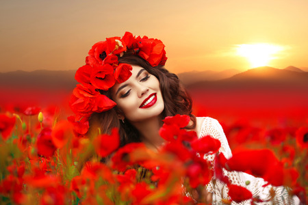 Portrait of beautiful happy smiling girl enjoying in red poppy field at sunset. Attractive young woman with red flowers on head. Makeup. Carefree woman. Wellness. Lifestyle. Stock Photo