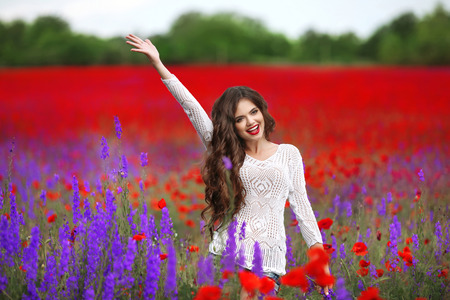 Beautiful young woman portrait in poppies field. Attractive brunette girl with long curly hair style in white dress walking and dreaming. Wellness. Lifestyle.
