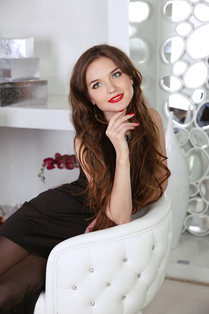 woman dress: Beautiful smiling woman with red lips and long hair sitting in modern armchair with fashion gems, indoor portrait