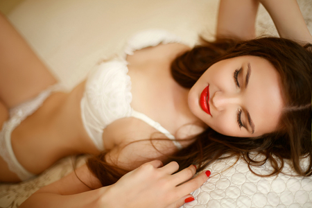 Beautiful alluring sensual girl in sexy white lingerie lying on the bed. Enjoying young woman. Stock Photo