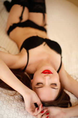 Beautiful alluring sensual girl in sexy black lingerie lying on the bed. Passion. Enjoying young woman.