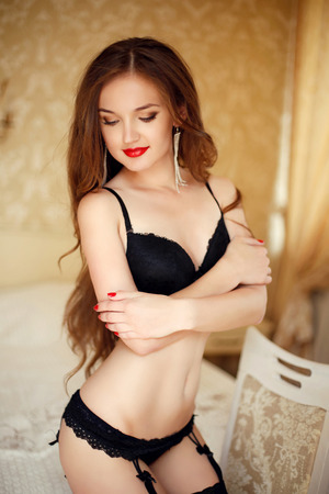Beautiful alluring young woman in sexy black lingerie in modern interior apartment.