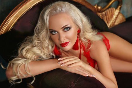 Beautiful fashion smiling woman with red lips makeup and wavy hair style, french manicured nails. Glamour lady posing on sofa. Stock Photo
