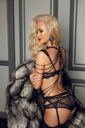 Beautiful alluring young woman in sexy black lingerie and luxury Necklace Shoulder jewelry. Glamour blond model posing on fur coat in modern interior.