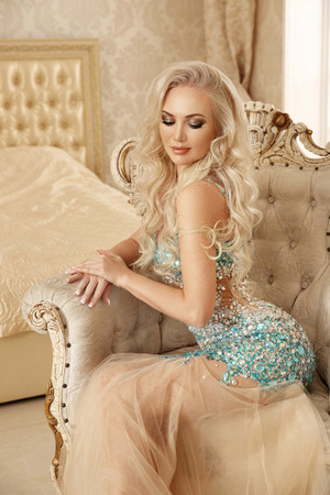 Beautiful sensual blond bride woman with makeup in luxurious dress with bijou gems, posing on modern armchair in luxury bedroom. Fashion indoor portrait