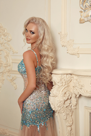 Beautiful gorgeous blond bride woman with makeup and long wavy hair style, posing in luxurious dress by modern wall in luxury interior. Fashion indoor portrait. Elegant lady.