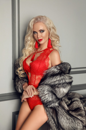 Fashionable blond woman in luxury fur coat wears in sexy red lace lingerie. Fashion Underwear. Beauty makeup and long curly hair style. Elegant lady in modern interior.