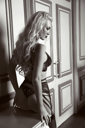 Sensuality, alluring sexy back of woman in black fashion lingerie posing by modern wall with frame in luxury interior. Stock Photo