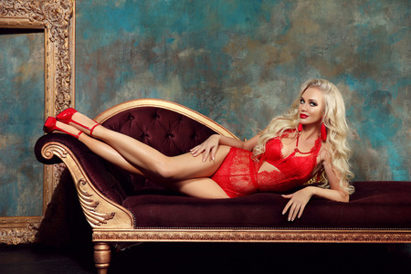 Beautiful alluring sexy woman portrait in red fashion lace lingerie lying on modern sofa with golden frame in luxury interior. Stock Photo