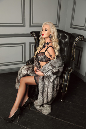 Elegant lady. Beautiful alluring sexy woman portrait in black fashion lingerie and fu coat, posing in modern armchair by wall with frame in luxury interior.