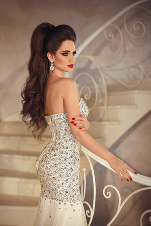 Beautiful elegant bride brunette woman with makeup and hair tail, gorgeous lady in wedding dress posing on front staircase in modern interior.