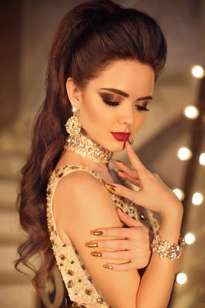 Beautiful brunette girl fashion portrait with Beauty makeup. Fashionable luxury golden jewelry. Long hair tail. Manicured nails. Elegand lady posing in modern interior.