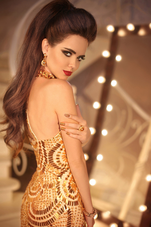 Elegant lady. Fashion brunette girl in golden dress. Beautiful attractive young woman posing by makeup mirror with bulbs in modern luxury interior.