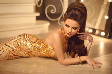 sexy glamour: Elegant fashion brunette woman in luxury golden dress. Hair style and red lips Makeup. Manicured nails. Sexy girl model lying in glamour gown in modern interior.