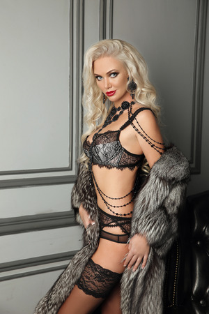 Beautiful alluring sexy woman portrait in fur coat, black fashion lingerie posing by modern wall with frame in luxury interior. Female in lacy panties, pendant jewelry.