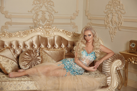 Beautiful alluring gorgeous woman in fashion dress lying on modern sofa with frame in luxury interior apartment. Elegant lady indoor photo style.