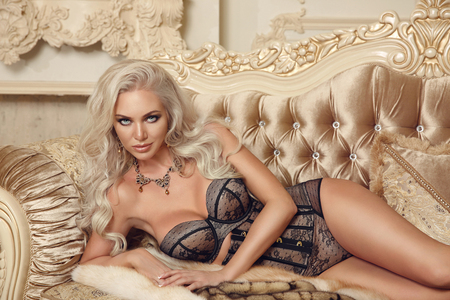 Beautiful alluring young woman in sexy lingerie lying on royal sofa in luxury modern interior. Beauty fashion style photo portrait.