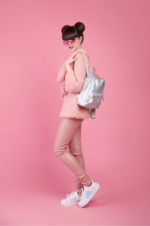 Fashion studio teen look style in shoes. Fashionable young girl wears in wool sweater and leather pants, holding backpack, posing isolated on  pink background.