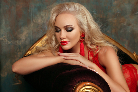 Beauty makeup. Beautiful fashion blond girl model with red lips, fashion earrings, blonde wavy hair style, french manicured nails. Glamour lady posing on modern sofa. Stock Photo