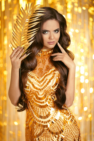 Elegant brunette in golden dress. Fashion style. Beauty makeup and wavy hairstyle. Beautiful smiling woman with long healthy hair style posing over gold bokeh party lights background. Stock Photo
