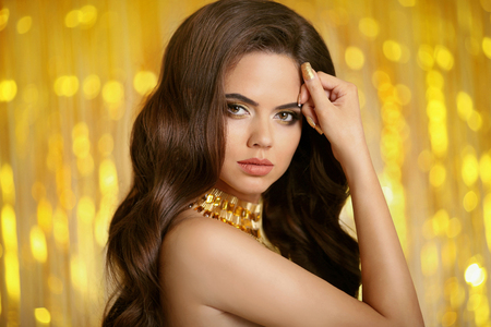 Healthy hair. Beautiful brunette woman portrait with long wavy hairstyle and makeup, lady wears in fashion golden jewelry isolated on Christmas party lights background. Stock Photo