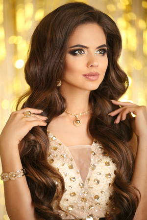 Beauty fashion woman in gold. Elegant brunette with makeup, long wavy hair style, pendant golden jewelry set. Fashionable glamour girl model in luxury over bokeh lights background. Stock Photo